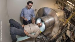 Image: two men, one of them is about to be driven in a tube – the prototype of the brain imager; Copyright: Sandia National Laboratories