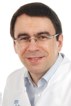 Image: Smiling physician with glasses, dark hair and white scrubs – Prof. Ali Yilmaz; Copyright: University Hospital Münster